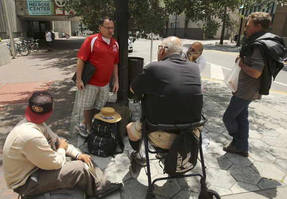 Homeless men sit outside the Orange County Public Library discussing issues with Advocate Brad Sefner. Photo courtesy Orlando Sentinel